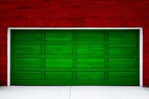 A green garage door on a red brick house